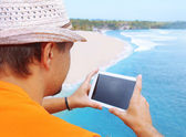 A man with tablet in hand on the beach — Stock Photo