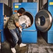 Young couple playing in an industrial laundry — Stock Photo #60273277