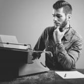 Young man with beard and mustache at the typewriter while smokin — Stock Photo