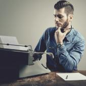 молодой человек с бородой и усами в пишущей машинке, куря — Стоковое фото