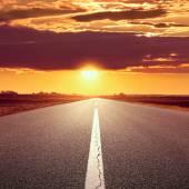 Dirigindo em uma estrada vazia ao pôr do sol — Foto Stock