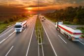 Two white trucks in motion blur on the highway — Stock Photo