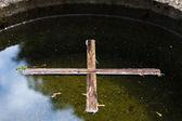 Wooden cross on water — Stock Photo