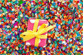 Little present on confetti — Stock Photo