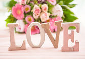 LOVE in front of flower bouquet — Stock Photo