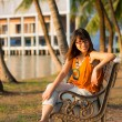 Cute Thai girl is relaxing near the riverside under the shade of the palm trees — Stock Photo #58271095