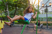 Children welfare. Cute Thai girl playing a swing — Stock Photo