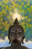 Buddha's Mercy. Buddha's statue looking down kindly with an aura on this head shining to console all living things — Stock Photo