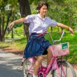 Asian Thai Schoolgirl student in school uniform playing risky on a bicycle, in the sunny summer season. — Stock Photo #73918571