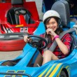 Cute Asian Thai girl is smiling with fun while driving Go-kart with speed from the starting point in playground racing track. Go kart is a popular leisure motor sports. — Stock Photo #73919739