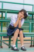 Cute Asian Thai schoolgirl student in uniform is sitting on a metal stand showing bashful and shy expression. — Стоковое фото