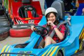 Cute Asian Thai girl is smiling with fun while driving Go-kart with speed from the starting point in playground racing track. Go kart is a popular leisure motor sports. — Stock Photo