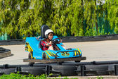 Cute Asian Thai girl is driving Go-kart car with speed in a playground racing track. Go kart is a popular leisure motor sports. — Stock Photo