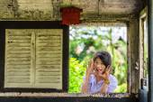 Cute Asian Thai schoolgirl student in uniform is making a surprise through the old retro window panel. Will anyone get frighten? — Stock Photo