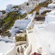 Two young people walking narrow streets of Oia — Stock Photo #75038403
