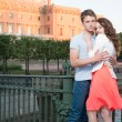 Young pretty couple embracing on the bridge near historical palace. — Stock Photo #51897715