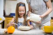 Small girl going to beat the dough for pancakes — Stock Photo