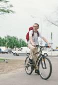 Man at bike on modern street — Stock Photo