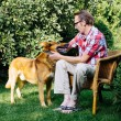 Man and his dog rest in the garden — Stock Photo #70075055