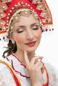Smile young woman hands on hips portrait in russian traditional costume -- red sarafan and kokoshnik.  — Stock Photo