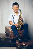 Six years old boy sit with saxophone on retro suitcases — Stock Photo