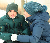 Older sister soothing younger crying brother on snow winter back — Stock Photo