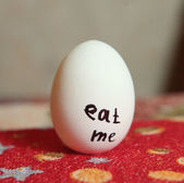 Boiled egg with the description eat me on the soft mat — Stock Photo