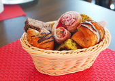 Pastry in the wicker  basket on the red mat  — Foto Stock
