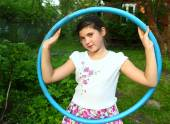 Preteen beautiful girl with hula hoop on the summer garden count — Stock Photo