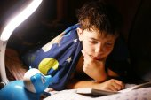 Preteen handsome boy read book with lamp before sleep — Stock Photo