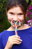 Teen girl with rainbow candy sticks close up portrait — Stock Photo