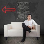 Asian businessman with phone on sofa — Zdjęcie stockowe