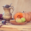 Still life with pumpkin, apples and metal pitcher. Arrangement on wooden table — Stock Photo #53982313