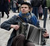Vilnius, Lithuania, March 4: young street musician playing in street musician even in Vilnius on March 4, 2015. Young unknown artist performing in the street. Musician passion — Stock Photo