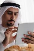 Arabský muž pomocí tabletu během snídaně — Stock fotografie