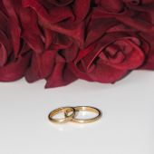Wedding rings with red roses — Stock Photo
