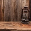 Lantern lamp old wooden table wall background — Stock Photo #64530007