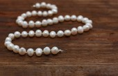 Pearls string wooden table closeup shallow DOF — Stock Photo