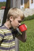 Boy drinks water from a red mug  — Stock Photo