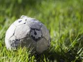 Old soccer ball on the grass — 图库照片