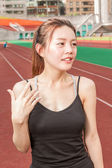 Chinese woman on sports track fanning herself — Stock Photo