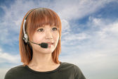 Call center operator with headset and blue sky and clouds in bac — Stock Photo
