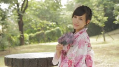 Asian woman in Japanese kimono fanning herself in Japanese style garden — Stock Video