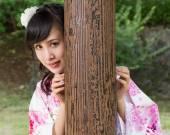 Asian woman in kimono behind wooden pillar — Stock Photo