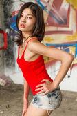 Beautiful Chinese woman by graffiti walls — Stock Photo