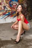 Piękna kobieta chiński przykucnęło przez graffiti ściany — Zdjęcie stockowe