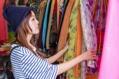 Asian woman looking at clothes on rack — Stock fotografie