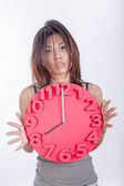 Tired Asian woman holding clock — Stock Photo