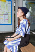 Asian woman at bus stop — Stock Photo