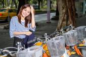 Chinese woman by rental bicycles — Stock Photo